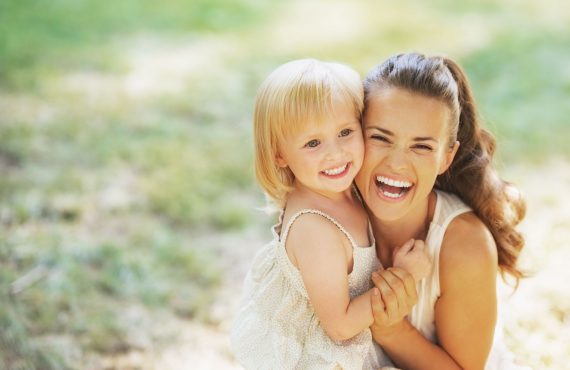Portrait of smiling mother and baby outdoors